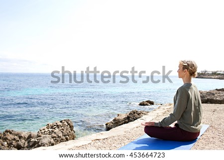 Side rear view of a mature woman sitting doing yoga position contemplating the sea on a sunny holiday exterior, beach and coastal destination. Healthy sporty senior woman, natural lifestyle outdoors. - stock photo