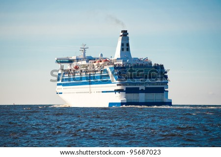 Side rear view of large modern cruise ship of ferry sailing in blue sea. - stock photo