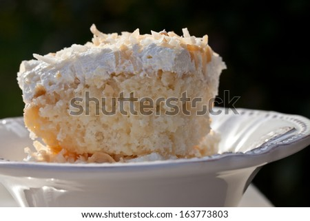 Side shot of a freshly cut slice of homemade coconut cream cake - macro shot - stock photo