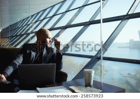 Side shot of handsome successful businessman pensively gazing out of the window thinking about the work plan, attractive young business man looking out of airport hall window, deep in thought - stock photo