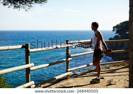 Side shot of handsome young runner stretching his legs before starting his run while standing on edge of a cliff with a wooden fence and enjoying ocean view from altitude - stock photo