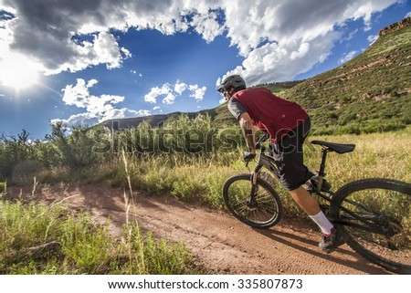 Side shot of mountain biker in red jersey with dramatic sky and  - stock photo