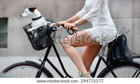 Side shot of woman and dog on bike - stock photo