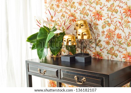 Side table with flowers and interior decoration next to bright window - stock photo