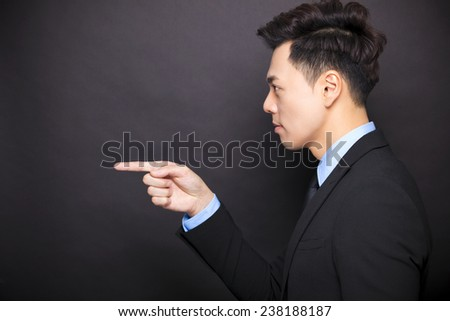 side view angry businessman standing before black background - stock photo