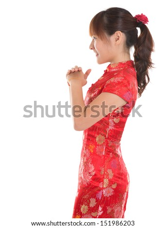Side view Asian woman with Chinese traditional dress cheongsam or qipao respecting on Chinese New Year Festival. Female model isolated on white background. - stock photo