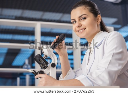 Side view. Attractive female scientist analysing something through a microscope in a laboratory. And looking at camera. - stock photo