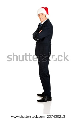 Side view businessman with folded arms wearing santa hat. - stock photo