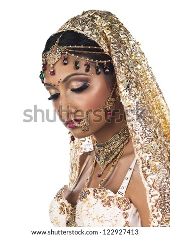 Side view close-up of an attractive young female wearing bridal costume and elegant jewelry over plain white background. - stock photo