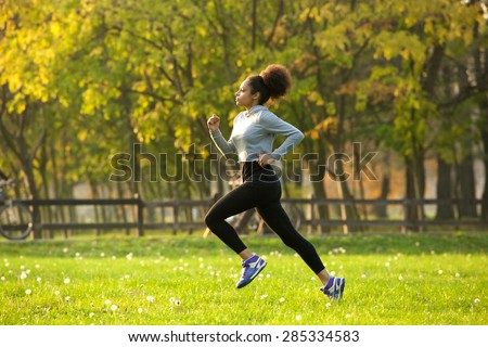 Side view full body portrait of a young woman jogging outdoors - stock photo