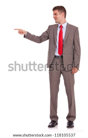 Side view, full length of a business man pointing at copyspace isolated over white background - stock photo