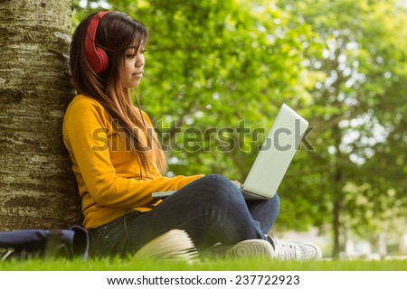 Side view full length of relaxed young woman using laptop in the park - stock photo