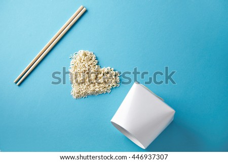 Side view I love wok takeaway noodles presentation with chopsticks, blank box and dry pasta in heart shape isolated on blue - stock photo