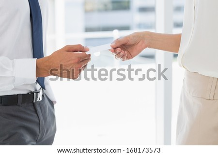 Side view mid section of two executives exchanging business card - stock photo