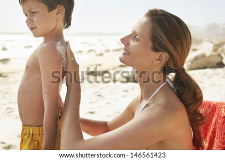 Side view mother applying sunscreen cream on son's back at beach - stock photo