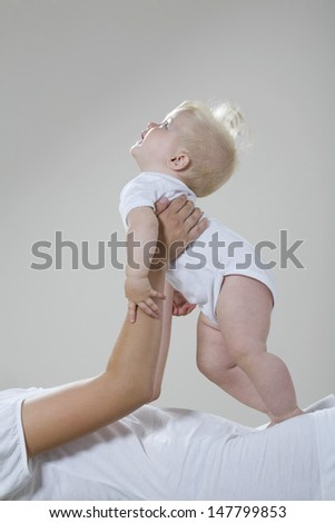 Side view of a baby girl resting in cropped mother's hands - stock photo