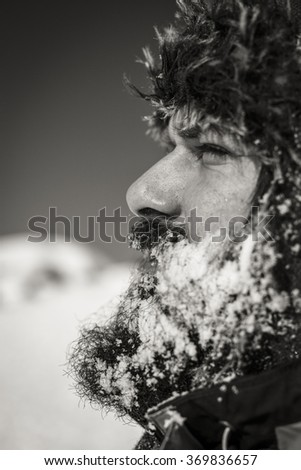 Side view of a bearded young man with hat in winter season.Monochrome  - stock photo