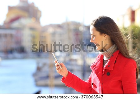 Side view of a beautiful happy woman wearing a red jacket using and texting a smart phone in winter outdoors - stock photo