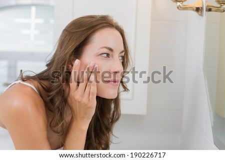 Side view of a beautiful young woman examining her face in the bathroom at home - stock photo