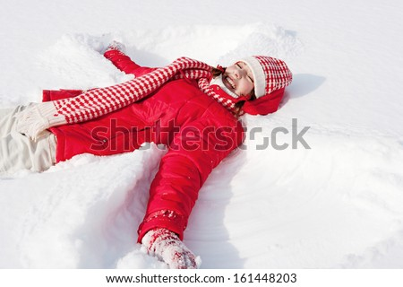 Side view of a beautiful young woman laying down on a frozen snow lake moving her arms up and down creating an angel figure shape, playing games while on vacation during a sunny winter day. - stock photo