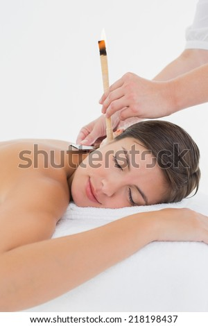 Side view of a beautiful young woman receiving ear candle treatment at spa center - stock photo