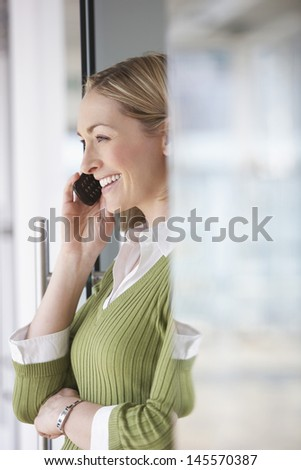 Side view of a blond businesswoman using mobile phone in office - stock photo
