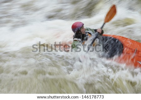 Side view of a blurred woman kayaking in rough river - stock photo