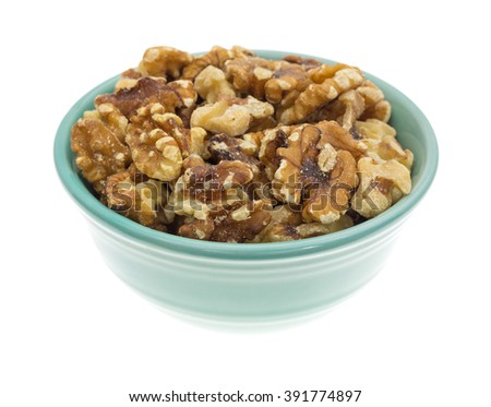 Side view of a bowl filled with shelled walnuts isolated on a white background. - stock photo