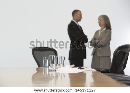 Side view of a business couple in discussion at conference room - stock photo