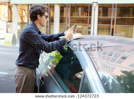 Side view of a businessman leaning on a car using a smart phone and taking notes in the city, wearing shades outdoors. - stock photo