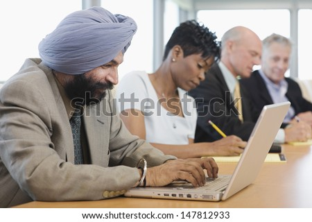 Side view of a businessman using laptop besides multiethnic colleagues in conference room - stock photo