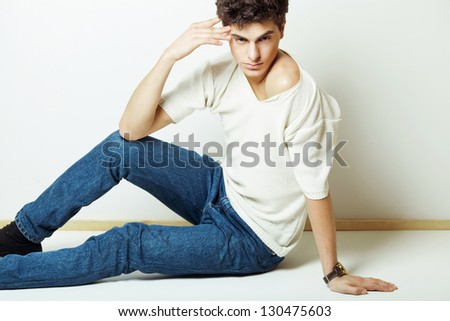side view of a casual fashion man sitting on white background and looking away from the camera - stock photo