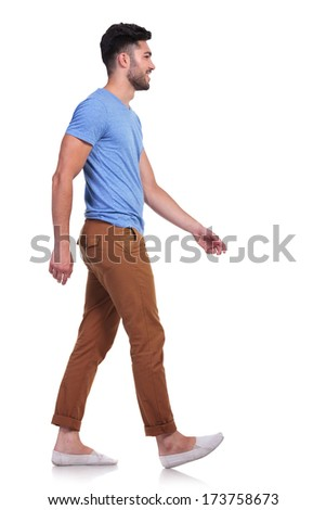 side view of a casual man walking forward and smiling on white background - stock photo