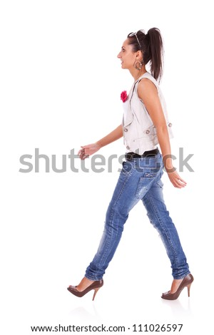 side view of a casual woman walking isolated over a white background - stock photo