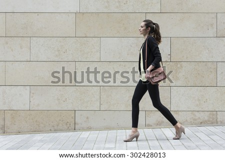 Side view of a Caucasian Businesswoman walking on city street in front of modern marble wall. - stock photo
