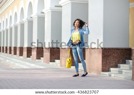 Side view of a Caucasian creative hipster woman in casual clothes walking on city street in front of modern marble wall. - stock photo