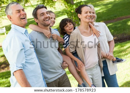 Side view of a cheerful extended family standing at the park - stock photo