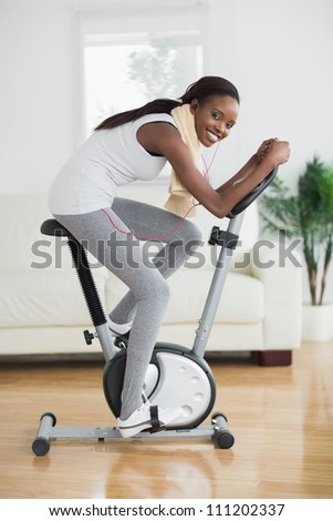 Side view of a concentrated black woman doing sport in a living room - stock photo