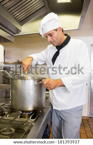 Side view of a concentrated male chef preparing food in the kitchen - stock photo