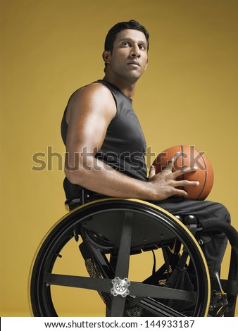 Side view of a confident paraplegic athlete in wheelchair holding basketball against yellow background - stock photo
