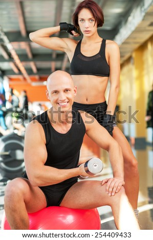 Side view of a couple exercising with dumbbells in the gym - stock photo