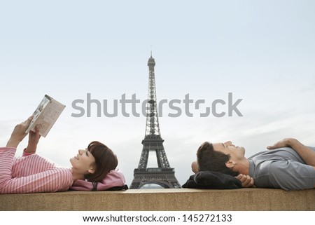Side view of a couple lying with Eiffel Tower viewed in the background - stock photo