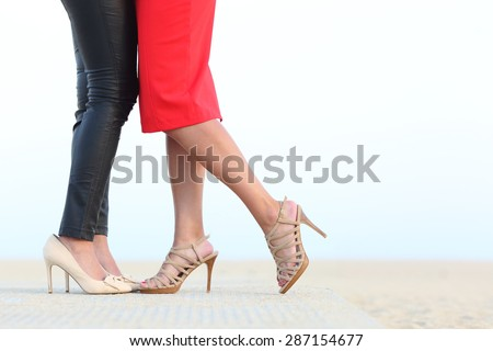 Side view of a couple of lesbian women legs cuddling with love on the beach - stock photo