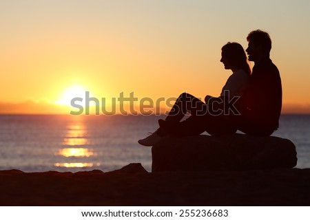 Side view of a couple silhouette sitting watching sun at sunset on the beach - stock photo