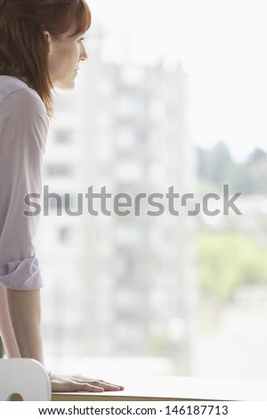 Side view of a cropped businesswoman looking out of window - stock photo