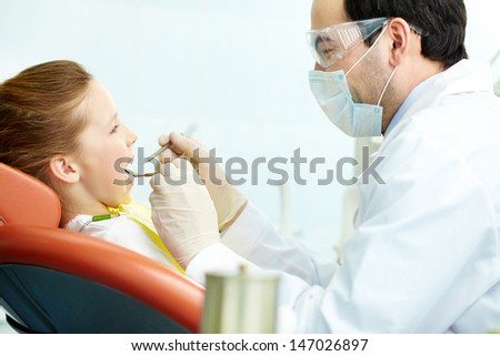 Side view of a dentist and his little patient - stock photo