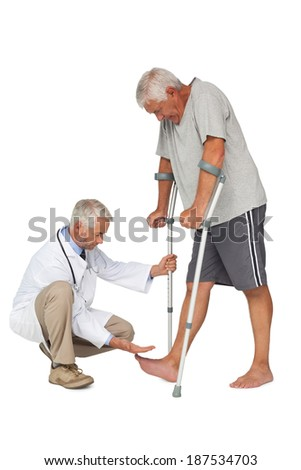 Side view of a doctor with senior man using walker over white background - stock photo