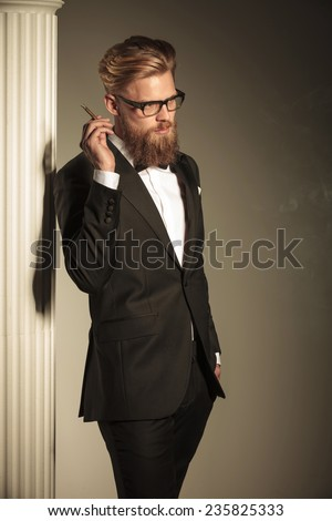 Side view of a elegant business man looking away from the camera while holding a cigarette in his hand. - stock photo