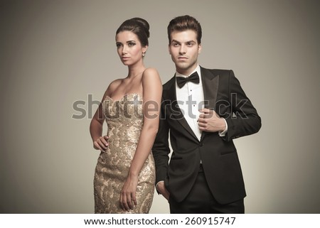 Side view of a elegant woman posing with her husband on grey studio background. - stock photo