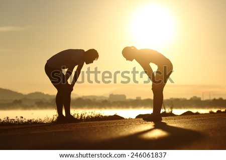 Side view of a exhausted and tired fitness couple silhouettes at sunset - stock photo
